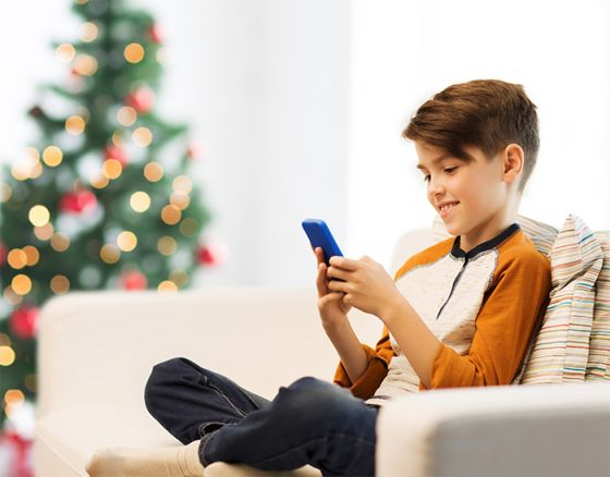 Young boy looking at smartphone with Christmas tree in background