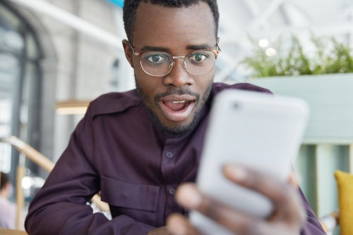 Young man looking surprised at smartphone
