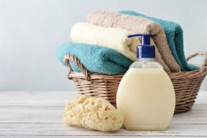 Liquid soap, sponge and towels in a wicker basket on a light background