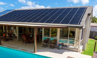 Solar panels on roof of house with pool