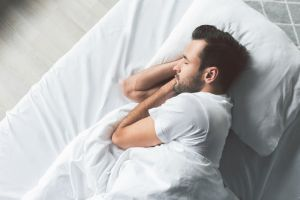 Man sleeping in bed with pillow