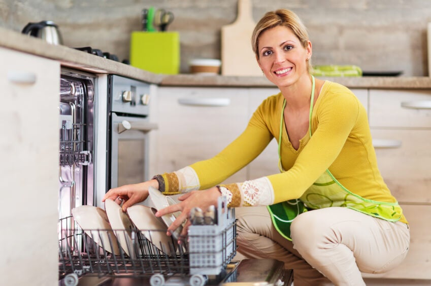 Smiling woman using dishwasher and looking at camera.