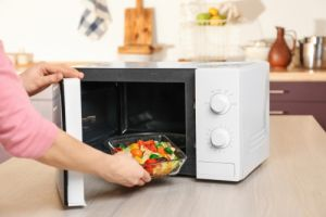 Woman-putting-bowl-with-vegetables-in-microwave