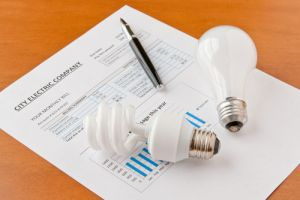 light bulbs on electricity bill with pen