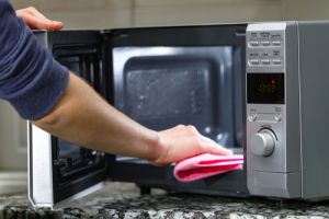 Housewife-cleaning-microwave-oven