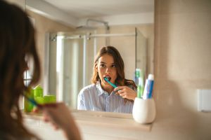 woman brushing teeth looking in mirror