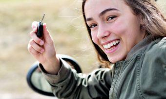 girl holding keys in car