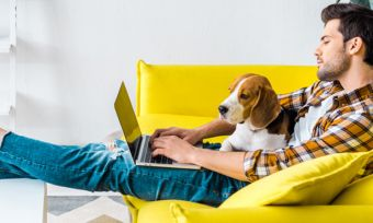 Man on laptop working from home with dog