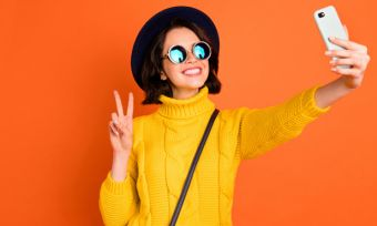 Young woman taking selfie against orange background