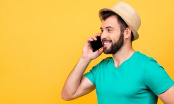 Man talking on phone against yellow background
