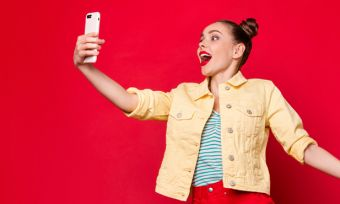 Young excited woman looking at phone against red background