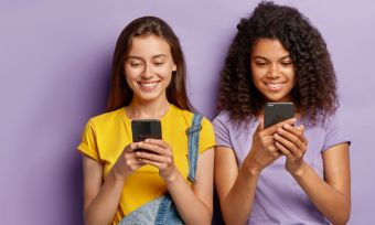 Two young women looking at phones against purple background