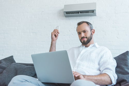 Man with laptop turning on air conditioner at home on lounge