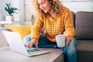 Lady sitting on couch with laptop and coffee