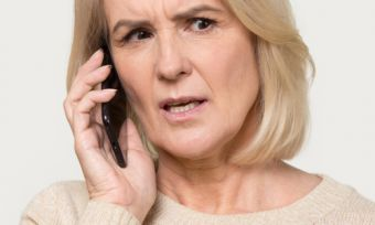 Mature age lady on phone to energy company frustrated