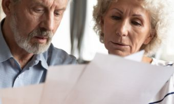 Mature age couple reading energy bills at table