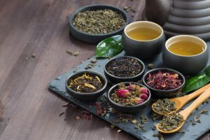 assortment of fragrant dried teas and green tea on dark wooden table