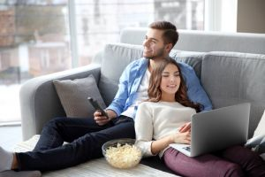 Young man watching TV and woman using laptop on a sofa at home