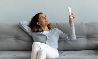 woman on couch with aircon remote