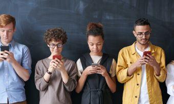 Group of people standing against dark wall looking at smartphones