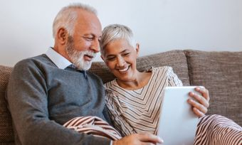 Older couple on sofa looking at tablet device
