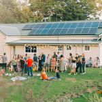 People having bbq in front of house with solar panels