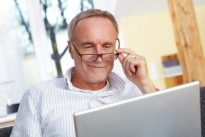 Happy boomer man looking at laptop for energy deals