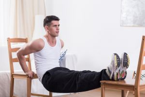 Man exercising at home with chairs