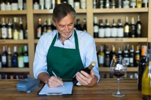 Small business owner at desk of wine shop looking at bottle
