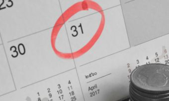 Calendar with date circled for bill payment with coins at forefront