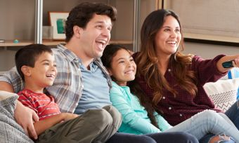 Young family sitting on sofa watching TV
