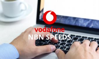 A man using a laptop behind the Vodafone Logo