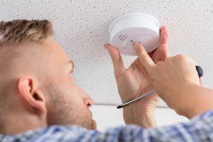 Man checking smoke alarm