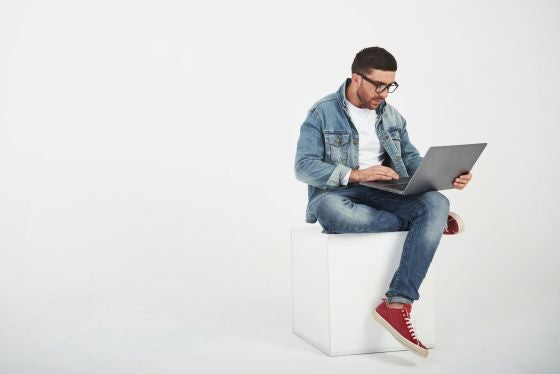 Person using a laptop in a white room