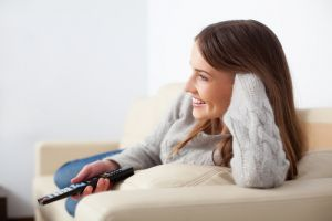 Young woman on couch with tv remote smiling