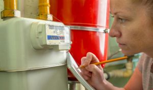 Lady with notepad writing down gas meter reading