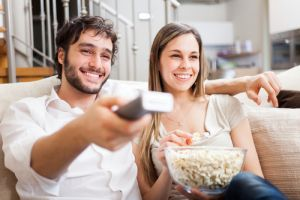 Young couple on couch watching tv with remote and popcorn