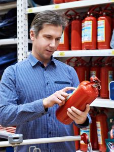 Man with a fire extinguisher in hand off shelf
