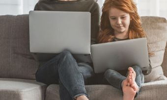 Young girl and mother using laptops