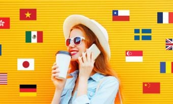 Young woman on phone against yellow background with various country flags
