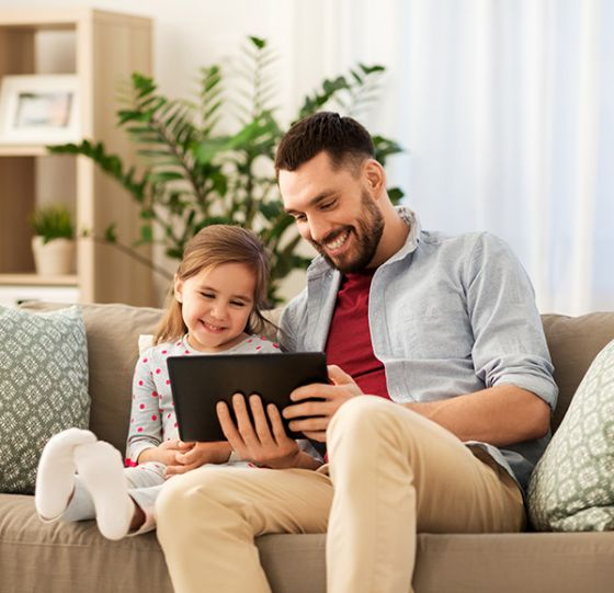 Father and young daughter watching video on tablet in the home