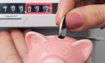 Hand putting coin in piggy bank with gas meter
