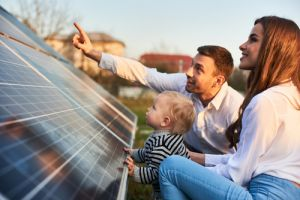 Young parents with child looking at solar panels at home