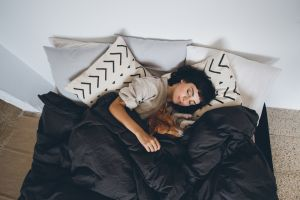 Woman in bed with doona