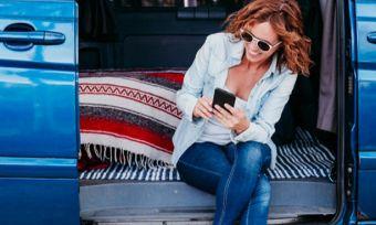 Travelling woman in van checking phone