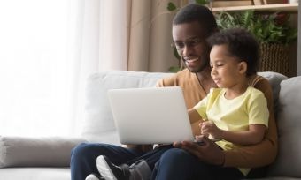 Young father with son looking at laptop while sitting on sofa