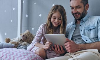 Father and daughter watching video on tablet