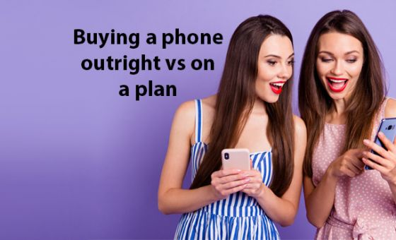 Young women looking at smartphones against purple background