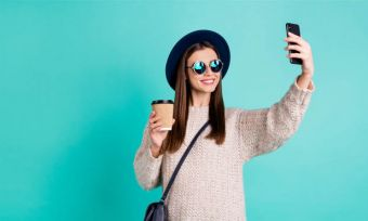 Young woman holding coffee and taking selfie against teal background