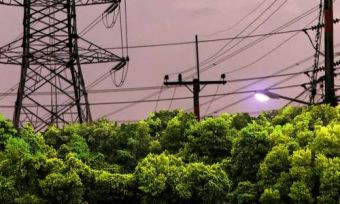Electricity towers and power lines over trees with stormy background